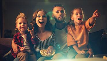 Красивая семья с двумя детьми смотрит фильм