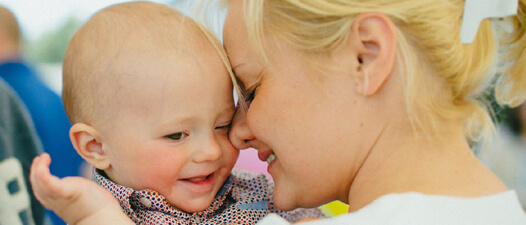Мама-блондинка обнимает своего ребенка