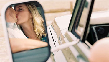 В отражении зеркала автомобиля влюбленные целуются